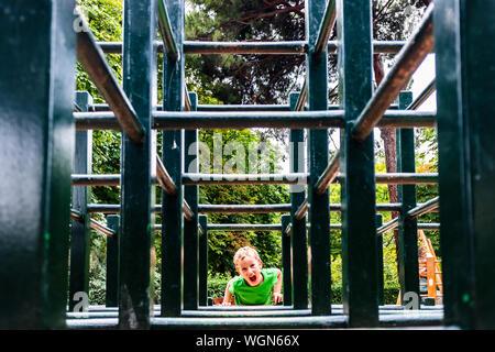 Junge spielt in einem Labyrinth von hölzernen Balken in einem Park. - Stockfoto