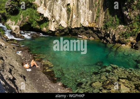 Knin, Sibenik/Kroatien 08-18-2019, schönen sonnigen Sommertag am Fluss Krka, junge Frau ruht in der Nähe der Wasser. - Stockfoto