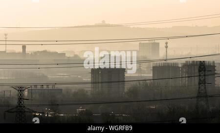 Stromleitungen gegen Gebäude in der Stadt während der nebligen Wetter - Stockfoto