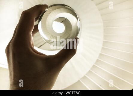 7/8 Hand der Frau mit Crystal Ball über Wendeltreppe - Stockfoto