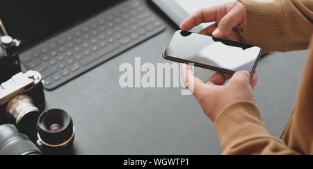 Nahaufnahme eines professionellen Fotografen berühren Smartphone in dunklen stilvolle Arbeitsplatz mit Kamera und Bürobedarf auf schwarzem Leder Schreibtisch - Stockfoto