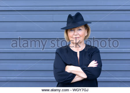 Portrait der älteren Frau, die gegen die Holzwand - Stockfoto