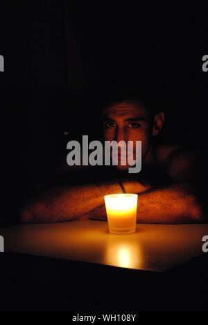 Portrait der junge Mann lehnte sich durch leuchtende Kerze auf dem Tisch in der Dunkelkammer - Stockfoto