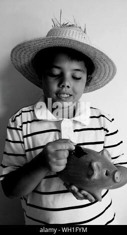 Junge mit Hut, Münze in Piggy Bank - Stockfoto