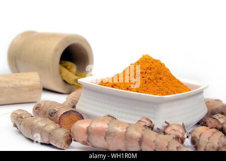 Frische Kurkuma Pulver in eine Schüssel und Kurkuma Wurzel, indische Gewürze eine gesunde und organische Bestandteile - Stockfoto