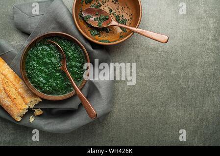 Essen Frühjahr gesunde Mahlzeit. Grüne cremige Suppe mit Gemüse und Kräutern und Brot - Stockfoto