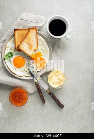 Frühstück serviert mit gebratenen Eiern, Brot, Marmelade, Butter und Kaffee auf den Tisch. Heathy Frühstück essen - Stockfoto