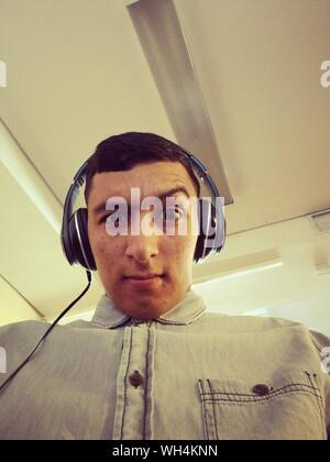 Porträt der Mann mit erhobener Augenbraue Musik hören über Kopfhörer gegen Decke - Stockfoto