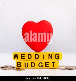 Nahaufnahme von roten Herzen mit Hochzeit budget Text auf Münzen - Stockfoto