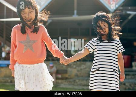 Portrait von lächelnden Schwestern halten sich an den Händen gegen Haus - Stockfoto