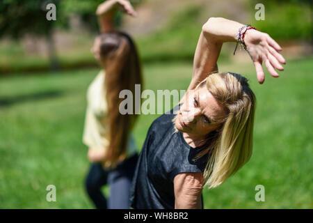 Reife frau yoga mit ihrer Tochter in einem Park - Stockfoto