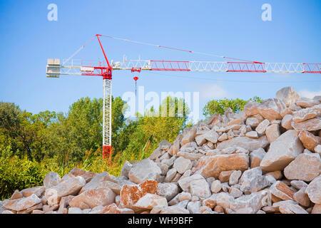 Stapel von Kies, Steine und Kiesel in verschiedenen Größen gegen einen Turm Kran - Stockfoto