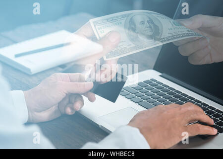 Doppelt belichtete Bild der Geschäftsleute mit Kreditkarte und Währung am Schreibtisch - Stockfoto