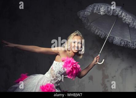 Porträt der schöne junge Frau in Rosa und weissen Brautkleid Posiert mit Regenschirm gegen die Wand - Stockfoto