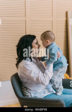 Eine junge Mutter in Jeans und ein weißes Hemd mit einem Baby auf dem Arm ist Spaß und Spielen. die Liebe der Mutter. Selektive konzentrieren. - Stockfoto