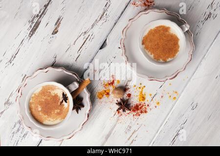 Zwei schöne Tasse traditionellen indischen Masala Chai Tee auf mit Sternanis und Zimt auf einem schäbigen Holz- Textur Hintergrund, Ansicht von oben. Zutaten: - Stockfoto