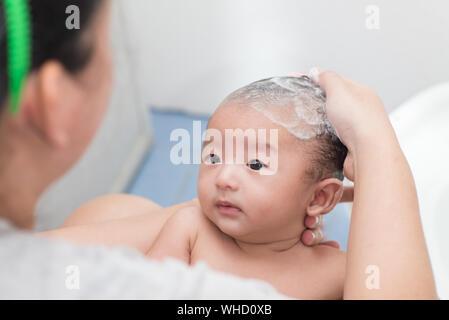Hohe Betrachtungswinkel von Mutter Baden Baby Boy zu Hause - Stockfoto