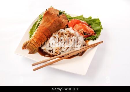 Hohe Betrachtungswinkel von Hummer mit Garnelen und Spaghetti in die Platte über der weißen Hintergrund - Stockfoto