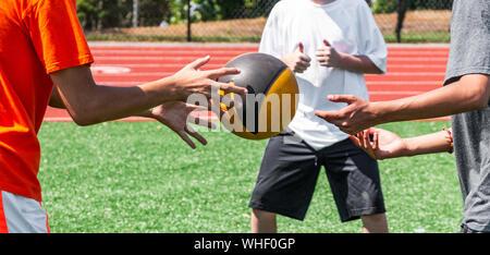 Drei Jungs im Teenageralter sind werfen einen Medizinball seitlich zueinander während Kraft und Beweglichkeit trainieren an der Praxis auf grünem Rasen. - Stockfoto