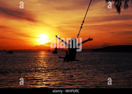 Silhouette-Boy schwingen über Meer gegen Orange Sky - Stockfoto