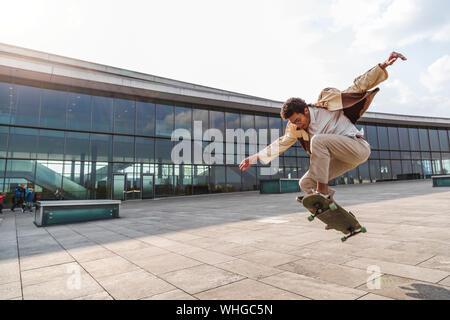 Afro mann Skateboarder fliegt in der Luft auf Skateboard - Stockfoto
