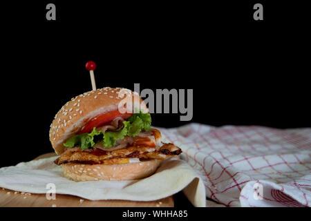 Burger mit Serviette und Schneidbrett auf Tisch auf schwarzem Hintergrund - Stockfoto