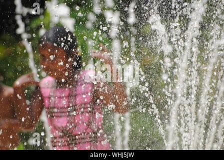 Mädchen spielen durch Brunnen gesehen, durch Wassertropfen - Stockfoto