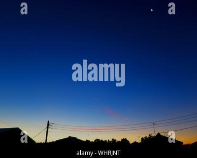 Low Angle View von Stromleitungen gegen den blauen Himmel am Morgen - Stockfoto