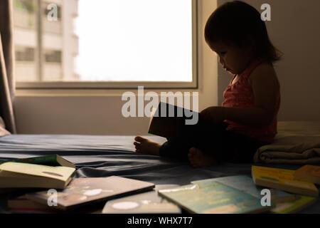 Ein kleines Mädchen, ein Buch auf ihrem Bett. - Stockfoto