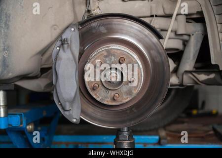 Eine Nahaufnahme am Bremssystem eines Autos mit der Bremsbeläge, der Scheiben, Bremssättel in einen Aufzug in einem Fahrzeug Werkstatt. Auto Service Industrie. - Stockfoto