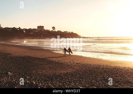 Silhouette Menschen mit Surfbrett zu Fuß am Strand gegen Himmel bei Sonnenuntergang - Stockfoto