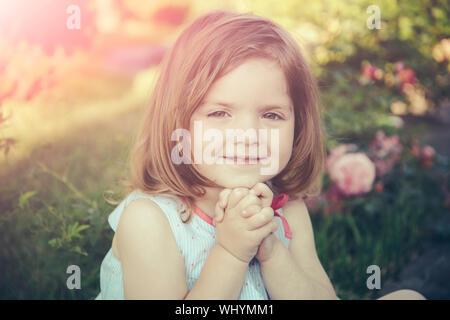 Keimung und Wachstum. Unschuld, Reinheit und Jugend Konzept. Kind an der blühenden rose Blumen auf grünem Gras sitzen. Mädchen lächelnd mit gefalteten Händen Ich - Stockfoto
