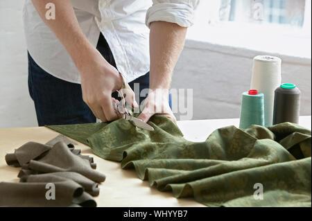 Mittelteil der jungen männlichen Maßgeschneiderte schneiden Stück Stoff am Tisch in der Mode studio - Stockfoto