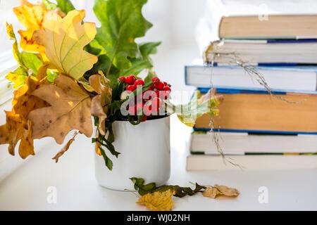 Herbst Komposition mit Stapel von Büchern und Strauß gelber Blätter und Zweige Mountain Ash in die Tasse. Herbst Jahreszeit Konzept - Stockfoto