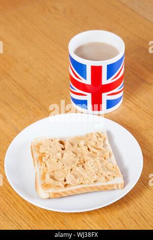 Britische Kaffeetasse und Scheibe Brot mit Butter auf Tisch - Stockfoto