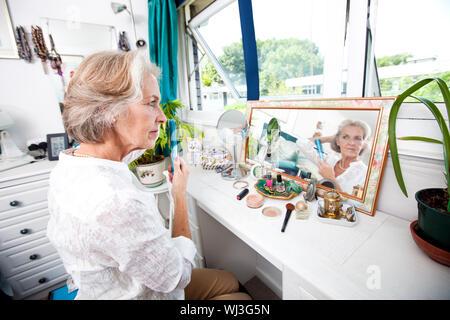 Ältere Frau kämmt am Kommode im Haus - Stockfoto