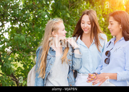 Drei schöne junge Mädchen Schüler Fuß in den Park, reden und lächeln gegen die Bäume. Kopieren Sie Platz - Stockfoto