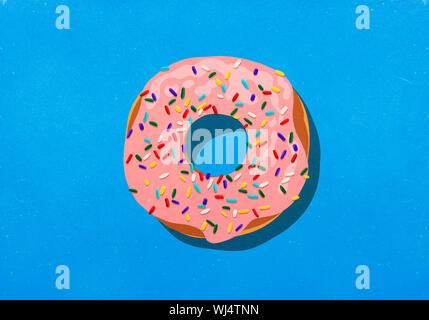 Rosa Donut mit Streuseln auf blauem Hintergrund - Stockfoto