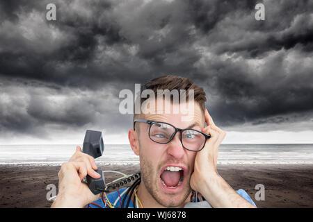 Das zusammengesetzte Bild im Hochformat von frustriert Computer engineer Schreien während eines Anrufs auf der Vorderseite des offenen cpu auf weißem Hintergrund - Stockfoto