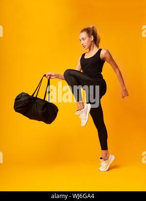 Junge Dame springen Holding Sporttasche auf gelbem Hintergrund - Stockfoto