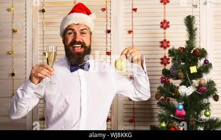 Mann mit Bart hält Champagner Glas und Weihnachtsbaum Kugel. Kerl in der Nähe von Weihnachten Baum auf Holz Wand Hintergrund. Santa Claus in Hut mit glücklichen Gesicht viele Grüße sendet. Feiern und das Neue Jahr Stimmung Konzept - Stockfoto
