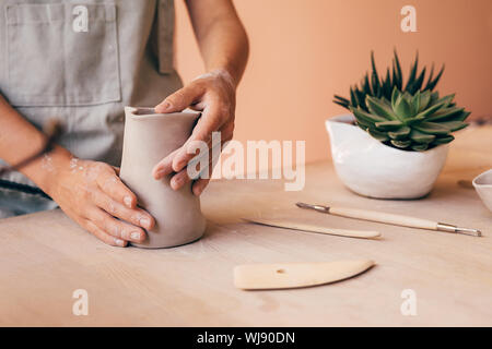 Handwerker molding Clay mit Händen auf einem Schreibtisch im Art Studio - Stockfoto