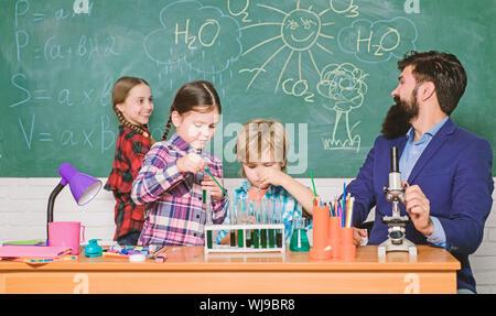 Wissenschaft ist immer die Lösung. Beobachten Sie die Reaktion. Schule Chemie Experiment. Faszinierende Chemie Lektion. Man bärtige Lehrer und Schüler mit Reagenzgläsern im Klassenzimmer. Erklären der Chemie zu Kindern. - Stockfoto