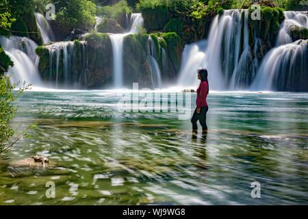 Seitenansicht der Frau Betrachten Wasserfall beim Stehen in der fließenden Fluss - Stockfoto