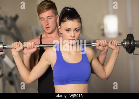 Trainer helfen fit Frau, heben Sie die Hantel in Turnhalle - Stockfoto
