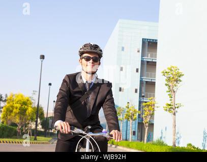 Geschäftsmann mit dem Fahrrad zum Arbeitsplatz zum Schutz der Umwelt - Stockfoto