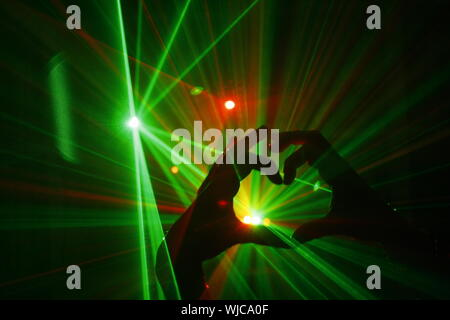 Zugeschnittenes Bild der Hände bilden Herzform gegen grüne Lichtstrahlen in Nachtclub - Stockfoto