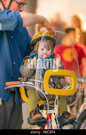 Vater mit Kleinkind im Fahrrad Kindersitz, Menningarnott oder kulturellen Tag, Reykjavik, Island. - Stockfoto