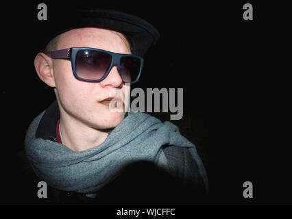 Junger Mann mit Sonnenbrille auf schwarzem Hintergrund stehend - Stockfoto