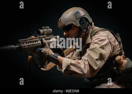 Mann mit Helm Holding Gewehr auf schwarzem Hintergrund - Stockfoto
